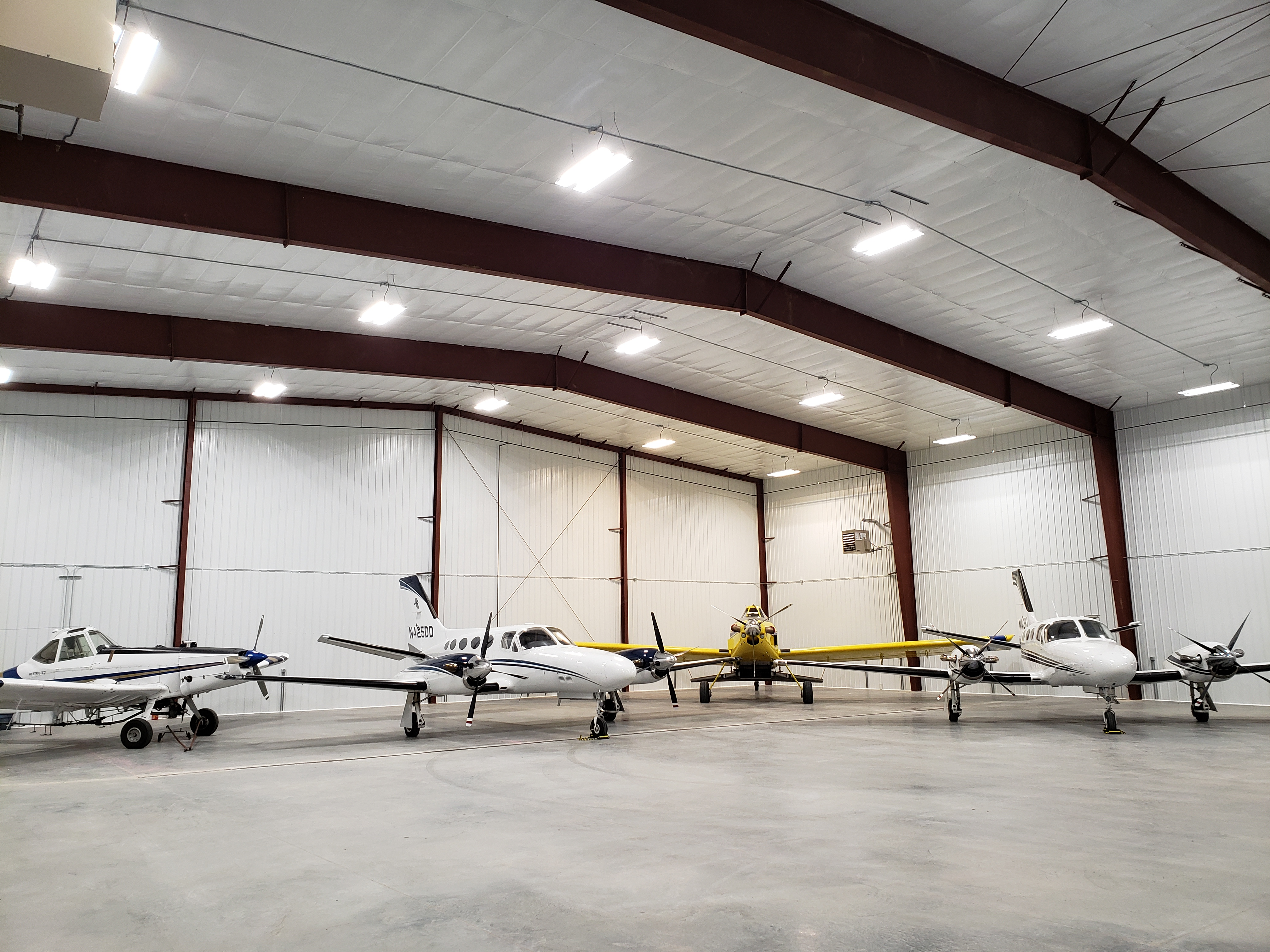 hangar with white planes and spray plane